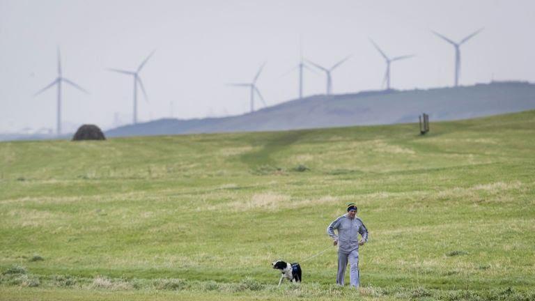 Foto de archivo de fecha 15/10/17 del hombre paseando a su perro cerca de Whitehaven en Cumbria.  Los planes aprobados para una nueva mina de carbón cerca de la ciudad de Cumbria producirán más emisiones que cualquiera de las otras actualmente abiertas en el Reino Unido, advirtió un grupo climático.  Fecha de emisión: sábado 30 de enero de 2021.